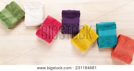 Colored Towels On A Wooden Background. Overhead With Copy Space