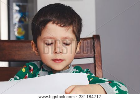 Cute Boy Reading Book On Chair At Home. Adorable Little Boy Opens White Page Of Exercise Book. Happy