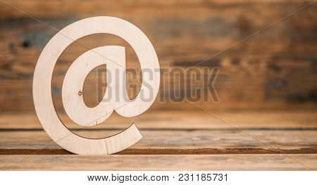 Wooden email symbol on grunge wood background