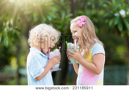 Kids Eating Ice Cream. Child With Fruit Dessert.