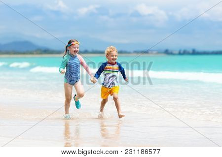 Kids On Tropical Beach. Children Playing At Sea.
