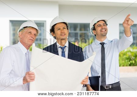 Closeup Portrait Of Three Content Diverse Business People Wearing Helmets, Holding Blueprint, Discus
