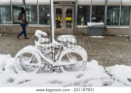 Montreal, Ca - 14 March 2018: Bike Covered With Fresh Snow In Front Of Berri Uqam Subway Station.