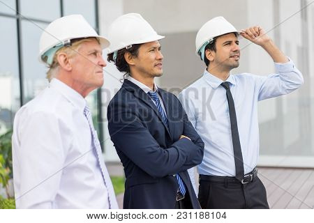 Closeup Portrait Of Three Focused Diverse Business People Looking Away, Wearing Helmets And Standing
