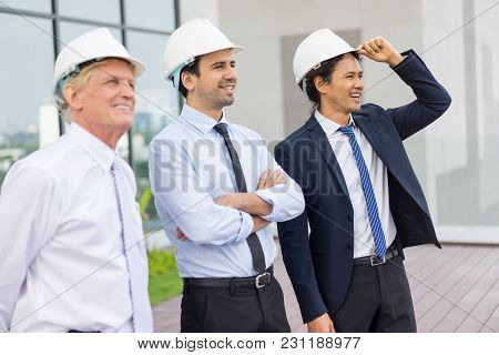 Closeup Portrait Of Three Smiling Diverse Business People Looking Away, Wearing Helmets And Standing