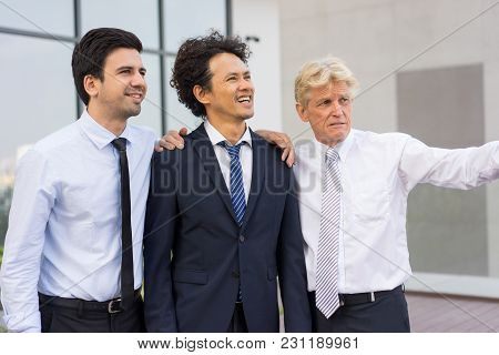 Closeup Of Business Team Of Three Positive Diverse People Looking At Something, Talking And Standing