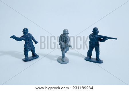 Three Plastic Toy Soldier On A Pop Vibrant Blue Background. Minimal Color Still Life Photography
