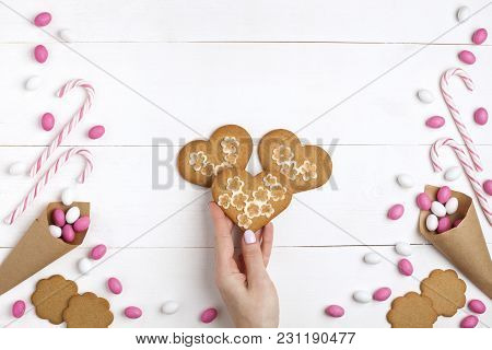 Frame Colorful Candies, Striped Lollipops And Cookies In The Form Of Heart Top View White Wooden Bac