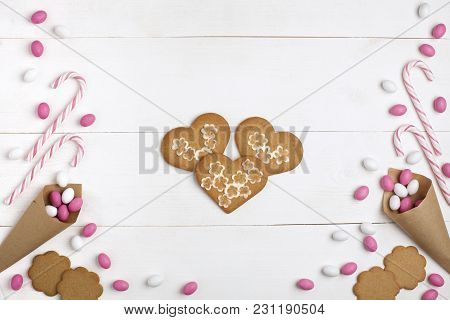 Frame Colorful Candies, Striped Lollipops And Cookies In The Form Of Heart In Hand Top View White Wo