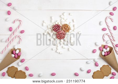 Frame Colorful Candies, Striped Lollipops, Cookies, Marshmallows And Lollipops Top View White Wooden