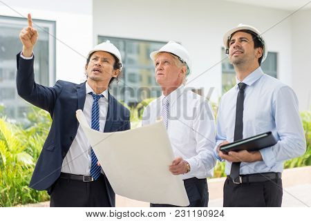 Closeup Portrait Of Three Serious Diverse Business People Wearing Helmets, Holding Blueprint, Discus