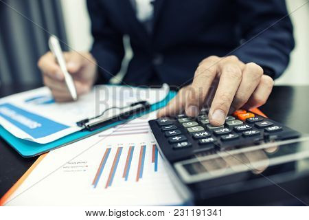 Man Using Calculator And Writing Make Note With Calculate