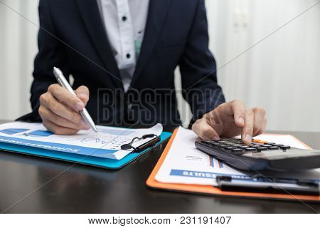 Man Using Calculator And Writing Make Note With Calculate In The Office