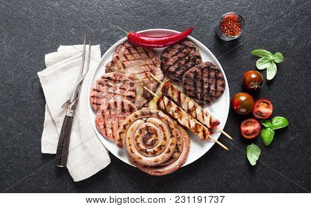 Meat Barbecue Party. Meat Grilled On A Plate, Basil Leaves, Tomatoes And Fork For Meat