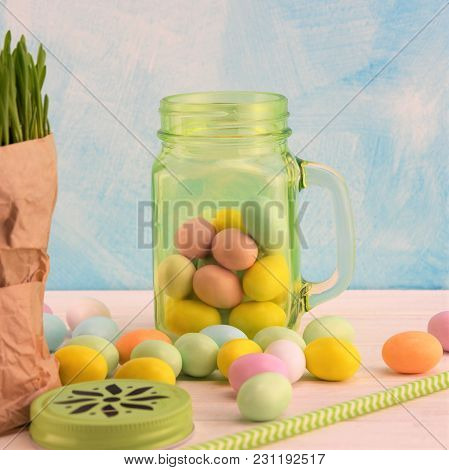 Green Transparent Glass Jar With Colored Easter Eggs And Straw On The White Wooden Table And Sky-blu