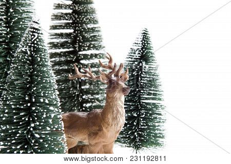 Isolated Group Of Full Artificial Firs Like A Small Forest Tree With A Figurine Reindeer Inside On A