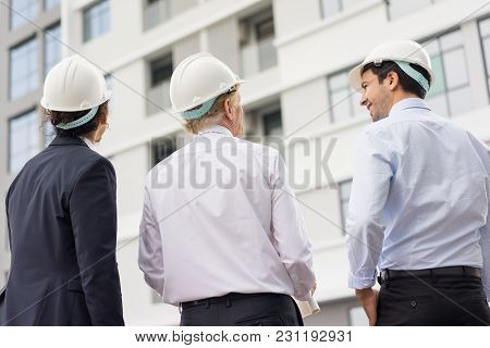 Closeup Portrait Of Three Diverse Business People Wearing Helmets And Standing Outdoors With Buildin
