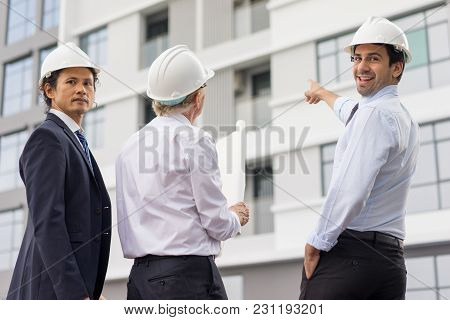 Closeup Portrait Of Three Diverse Business People Wearing Helmets, Looking At Camera And Standing Ou
