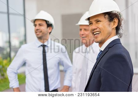 Closeup Of Three Happy Diverse Business People Looking Away, Wearing Helmets And Standing Outdoors W