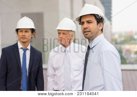 Closeup Of Three Serious Diverse Business People Looking Away, Wearing Helmets And Standing Outdoors