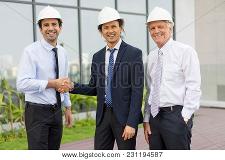 Closeup Portrait Of Three Smiling Diverse Business People Looking At Camera, Wearing Helmets, Shakin