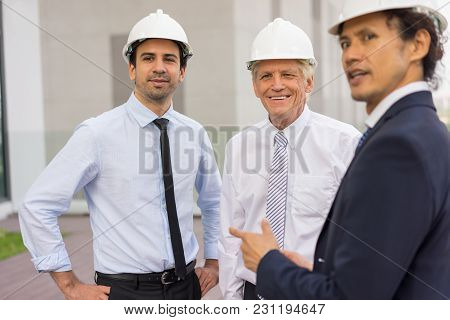 Closeup Of Three Smiling Diverse Business People Wearing Helmets And Standing Outdoors With Building