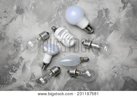LED, incandescent and fluorescent lamps on grey background
