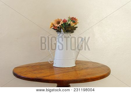 Designer Creative Vase In The Form Of A White Teapot With Flowers On The Table