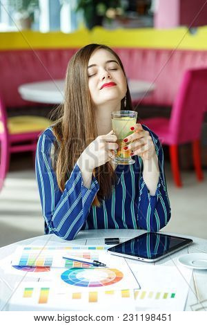 A Tired Business Woman Drinks Tea At A Break. The Concept Of Work, Business, Education, Freelance, L