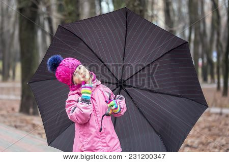 Little Cute Caucasian Girl In Hat And Jacket Walking Under Umbrella In A City Park Guess Whether It