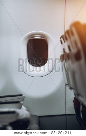Vertical Shoot With A Shallow Depth Of Field Of The Porthole Of Modern Business Aircraft During A Ni