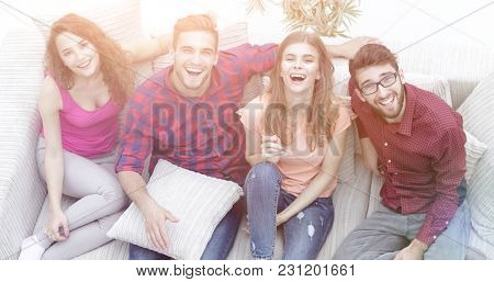 four happy friends laughing while sitting on the couch