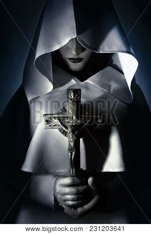 Praying Woman In White Hooded Cloak Holding A Cross.