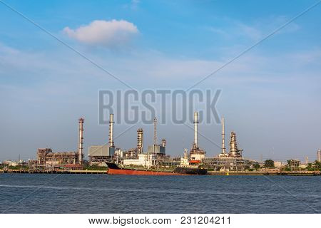 Oil And Gas Refinery Plant With Shipping Loading Dock At Daylight
