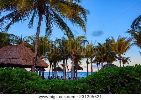 Palm Trees And Tropical Huts At Dusk In Playa Del Carmen Mexico.