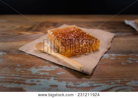 Block Of Honey Comb And Spoon On Wooden Table