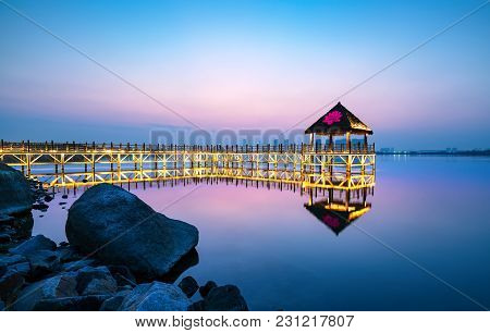 Tranquil Lake And Wooden Trestle, Evening Landscape.