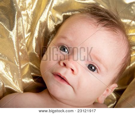 Closeup Portrait Of Baby Boy On Gold Background