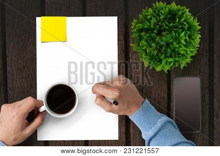 Man drinking coffee on a piece of paper
