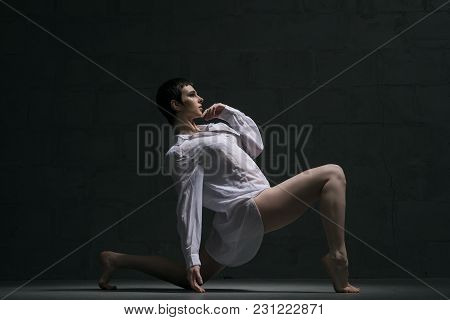 Girl With Shot Haircut In Sexy White Shirt Dancing Gracefully In Dark Room Full-length Profile Shot