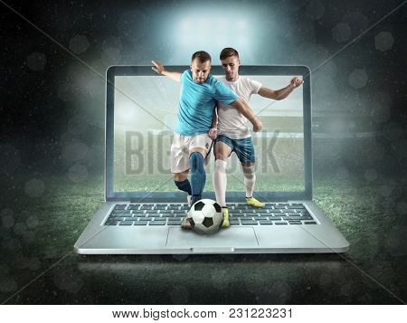 Caucassian soccer Players in dynamic action with ball in a professional sport game play on the laptop in football under stadium lights.