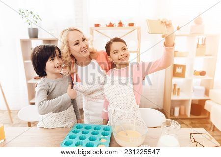 Young Beautiful Grandmother, Along With Her Grandchildren, Makes Selfie Phone In Kitchen. Beautiful