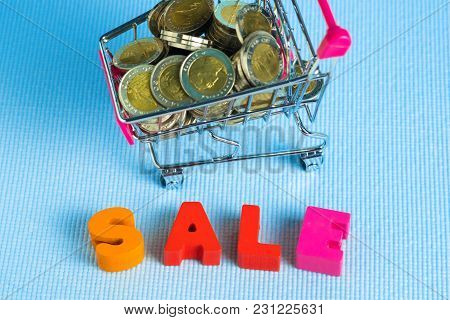 Sale Colorful Wooden Text And Shopping Cart Or Supermarket Trolley On Blue Background With Copy Spac