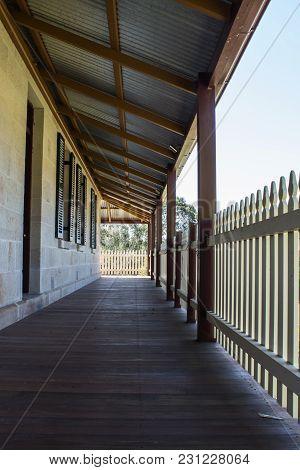 Outdoor Verandah Patio Deck Of Sandstone Brick Cottage With Picket Fence In Sunshine
