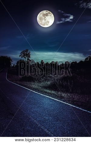 Beautiful landscape of dark sky with bright full moon and asphalt roadway through suburban zone. Serenity nature background, outdoor at nighttime. The moon taken with my own camera. poster