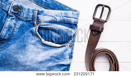 male jeans and leather belt on wooden background, top view