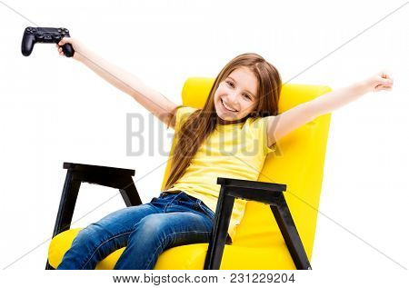 Happy girl in a yellow chair holding up playing console, winning a computer game