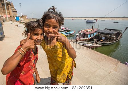 VARANASI, INDIA - MAR 14, 2018: Unidentified indian children on the banks of Ganga river. Varanasi is most important pilgrimage sites in India, one of the 7 sacred cities of Hinduism.
