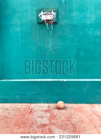 Concrete basketball field with damaged net and ball