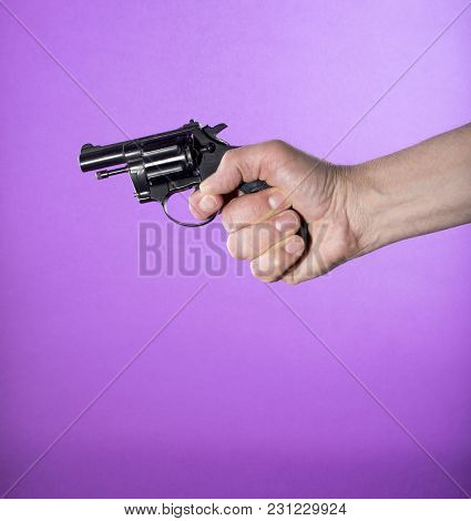 Revolver In A Man's Hand On A Purple Background